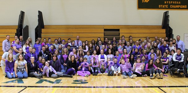 photo of middle school Students and staff wearing purple sitting together in gym