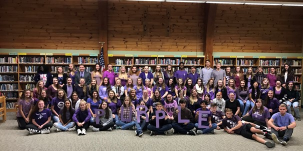 photo of High School students all wearing purple in the library