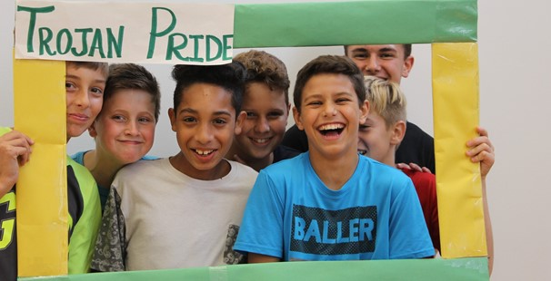 photo of middle school boys holding a Trojan Pride frame