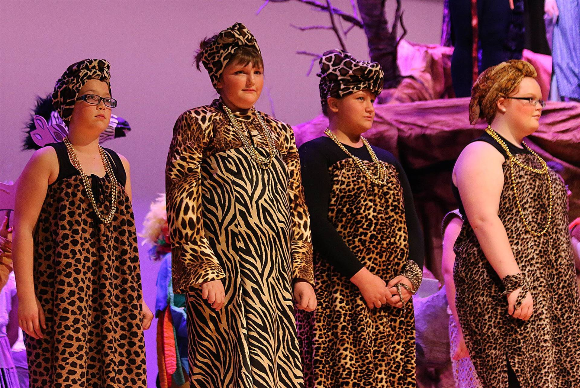 Four students in tribal costumes during the Lion King play