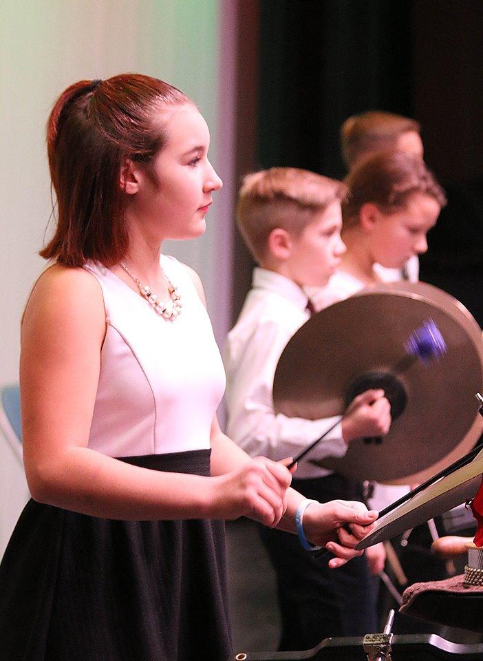 Girl holding drumsticks during band concert