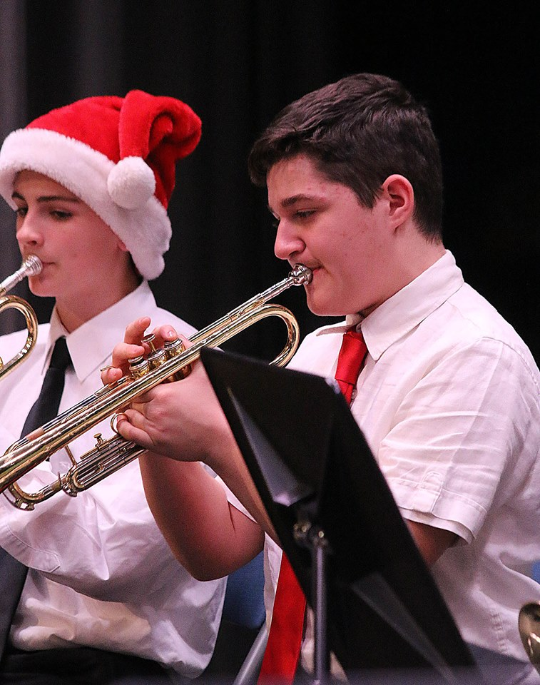 Two boys playing trumpets, one in a Santa hat, at Holiday Band concert