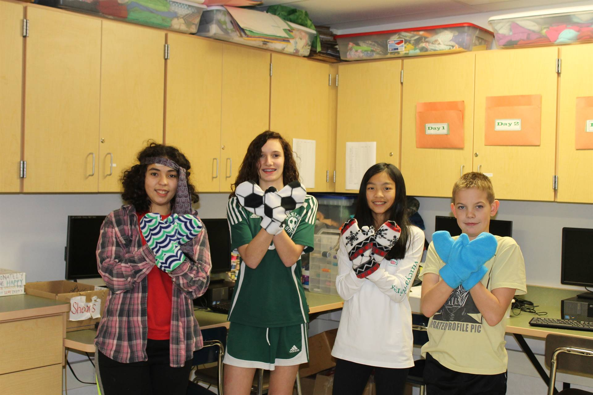 8th grade students wearing mittens they made in FACS