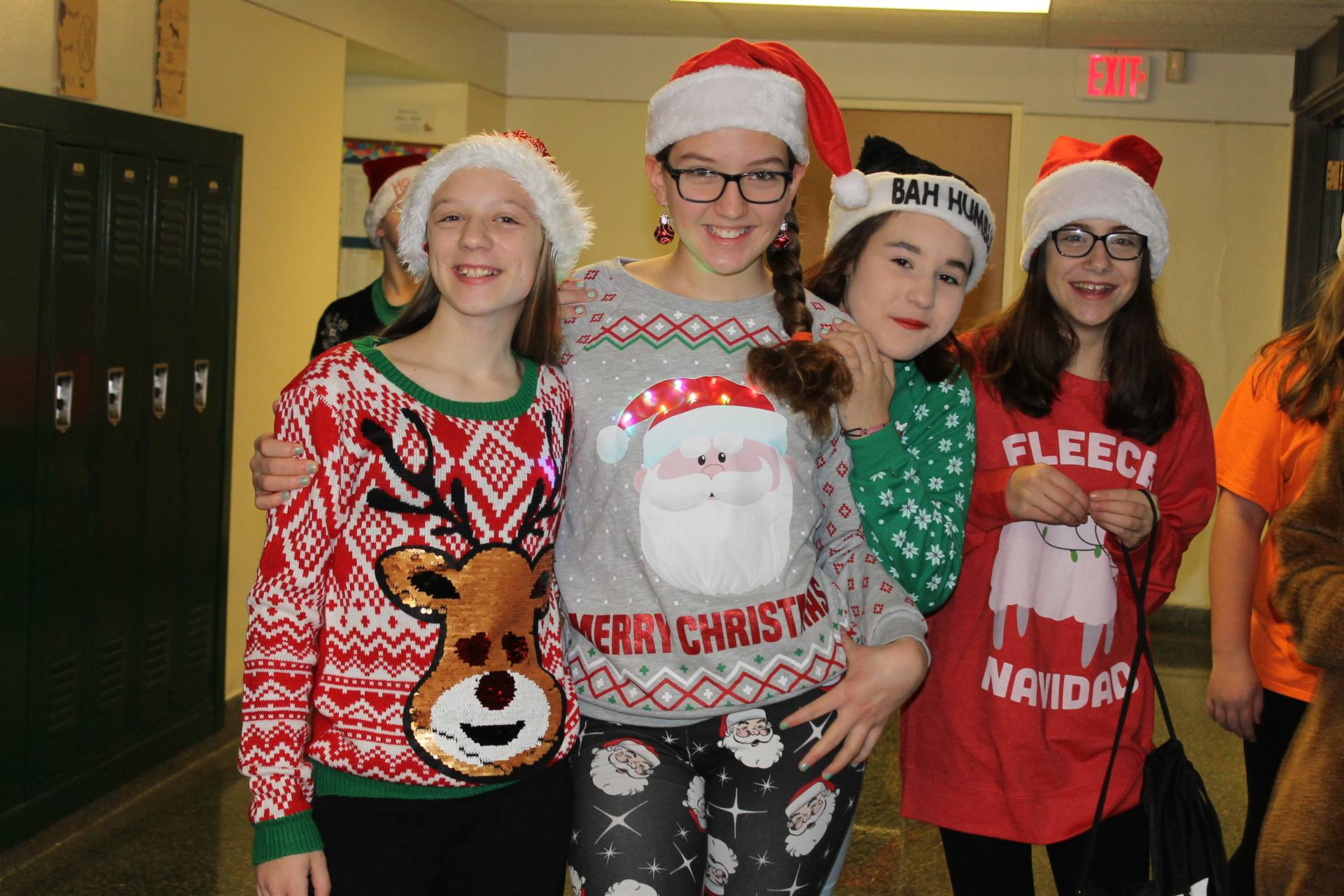"""Four girls showing off their """"ugly sweaters"""" on Spirit Day"""