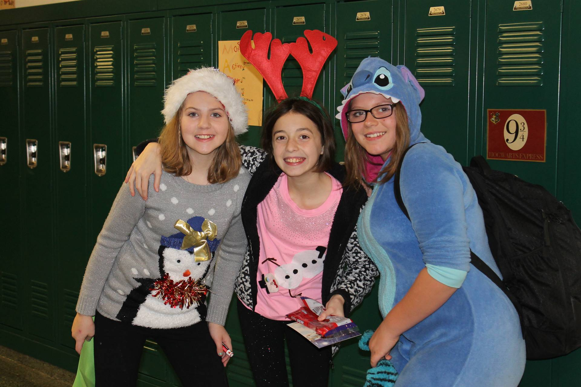 Three girls together in front of the lockers on Spirit Day