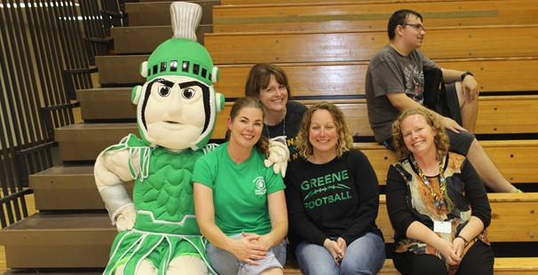 Photo of Trojan mascot with high school staff sitting on bleachers