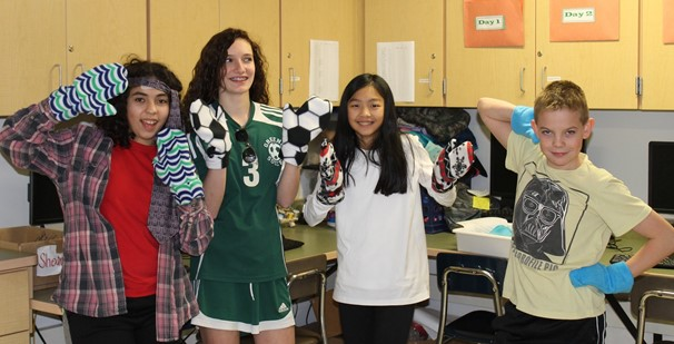 photo of four 8th grade students wearing mittens they made