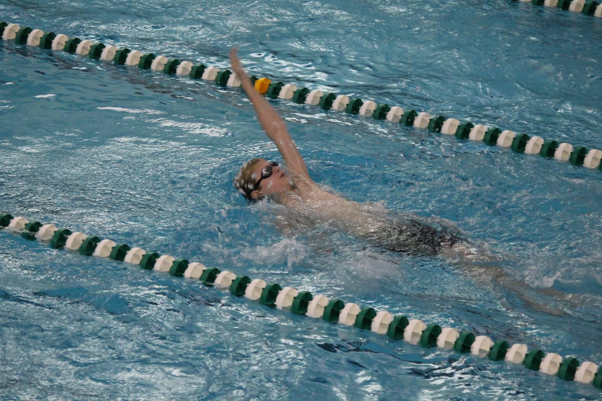 Boy doing backstroke during swim meet