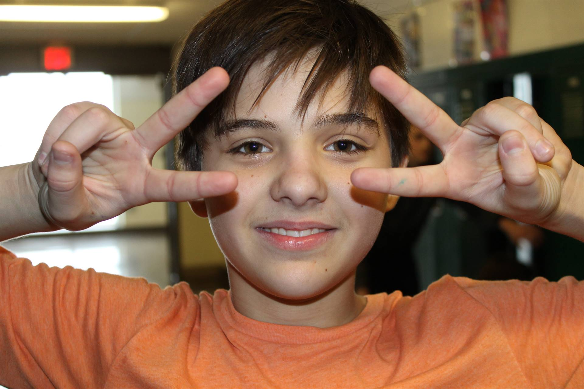 """Boy making """"Peace"""" sign with hands by his face"""