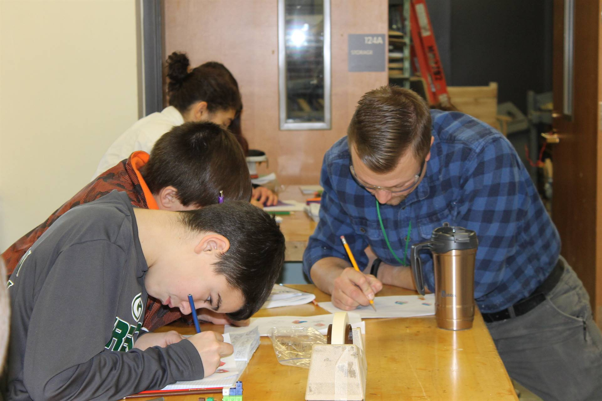 Students and teacher writing at table