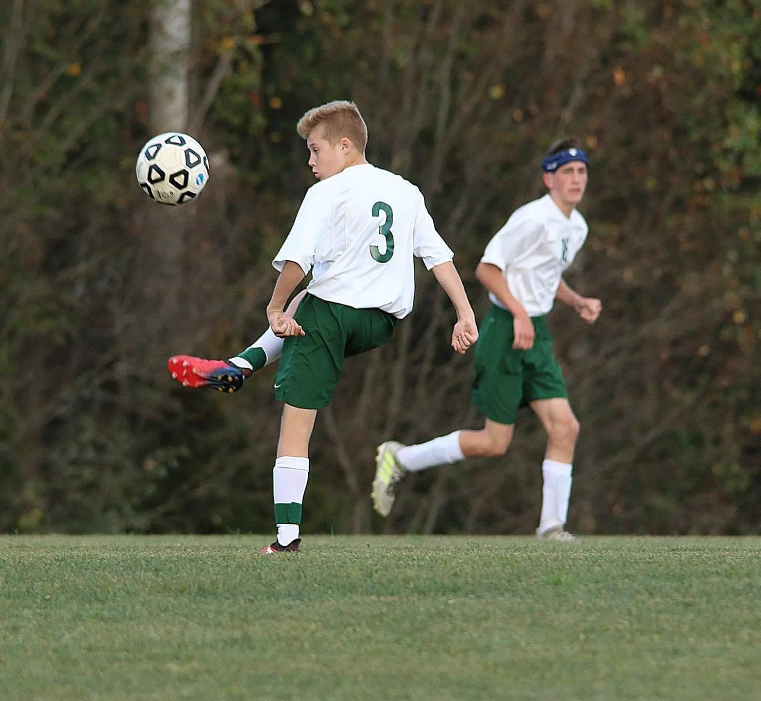 8th grade boy kicking a soccer ball during a game