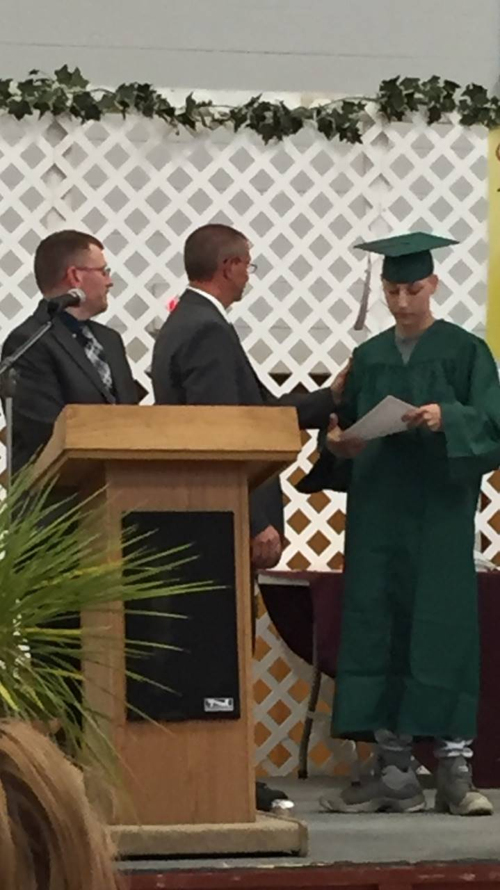 photo of male high school student receiving diploma