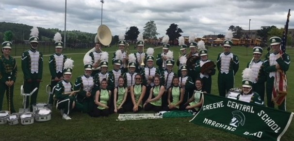 photo of the Greene Marching band sitting in the grass in their uniforms