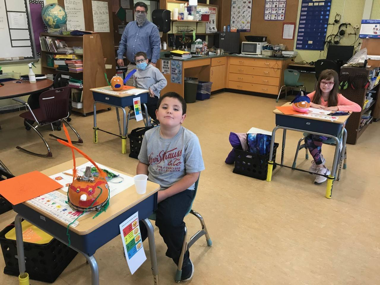 Photo of Mr. Evans' students painting pumpkins and writing about their creations