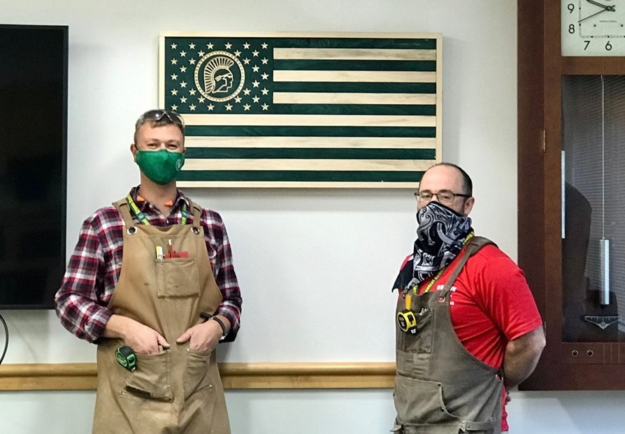 Photo of Mr. Bogardus and Mr. Dotson with wooden flag they created for District Office