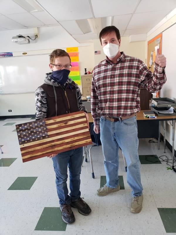 Photo of Sam Cowen and Mr. Connelly with wooden flag made by Sam